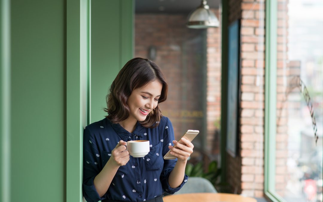 A businesswoman in the cafe uses a mobile phone and drinks coffee and smiles