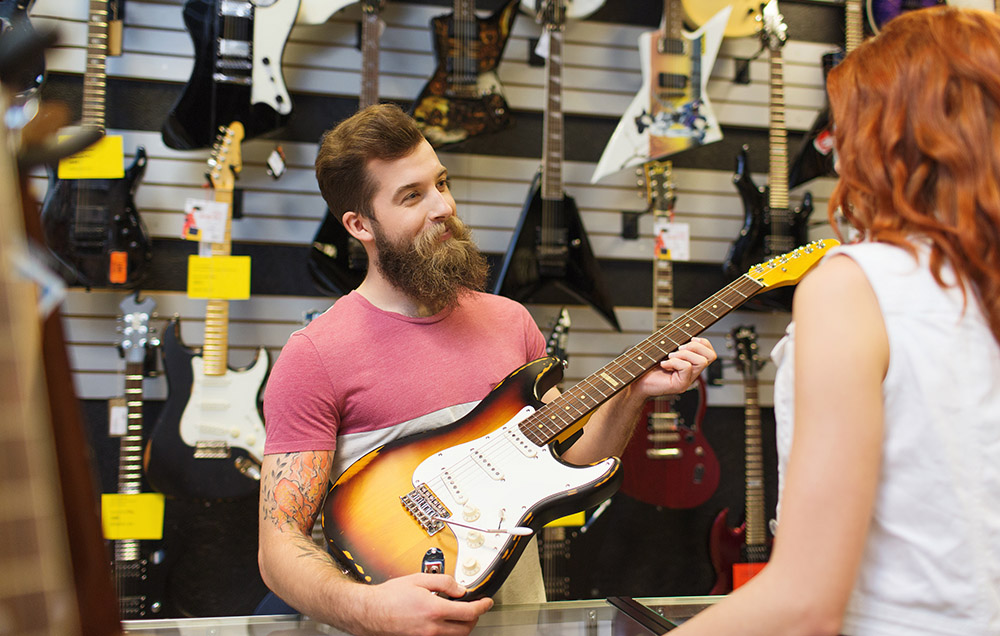 Male assistant showing customer guitar at a pawn shop
